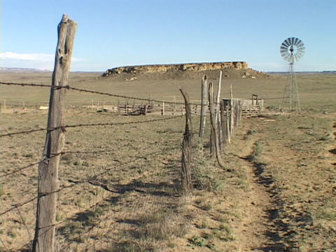 A barbed wire fence stretches across a prairie towards a windmill and a desert butte Footage