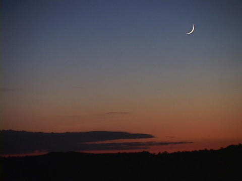 A pale sliver of moon hangs in a blue and orange sky Live Action