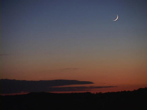 A pale sliver of moon hangs in a blue and orange sky Stock Video Footage