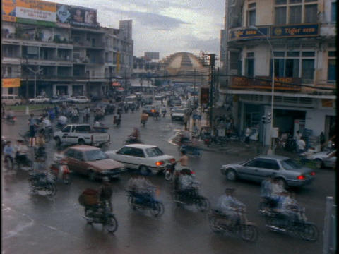 Traffic drives through a crowded intersection Stock Video Footage