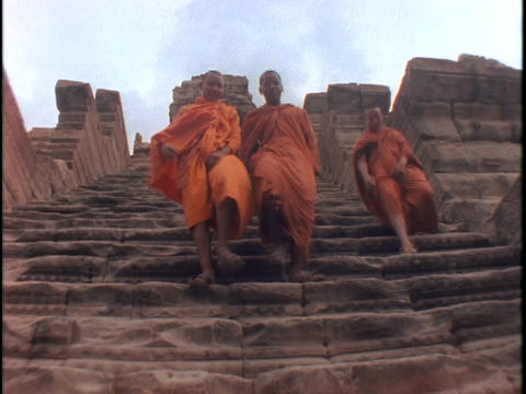 Buddhist monks climb down steps Stock Video Footage