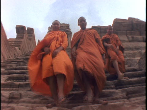 Buddhist monks climb down steps Footage