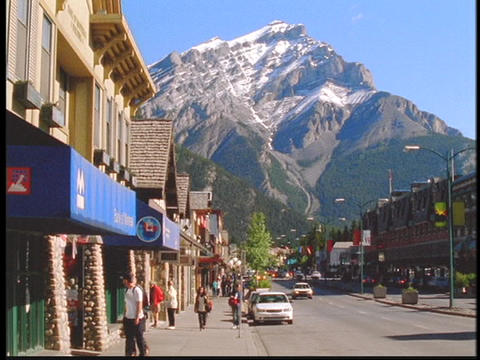Tourists wander between shops in a small resort town beneath the Canadian Rocky Mountains Footage