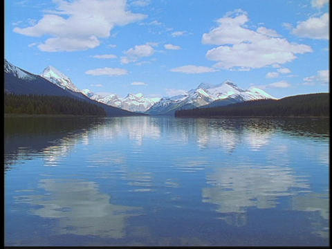 The Canadian Rockies and clouds reflect in a lake Stock Video Footage