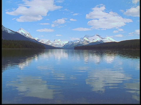 The Canadian Rockies and clouds reflect in a lake Footage