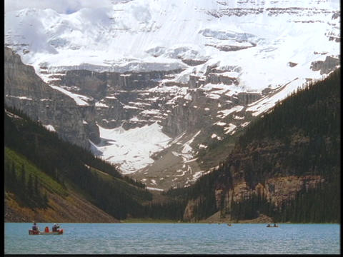 Boaters float in Lake Louise past the Canadian Rockies Stock Video Footage