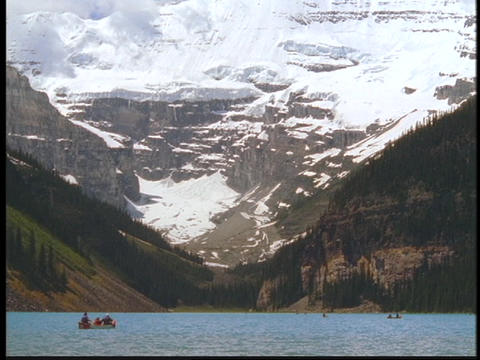 Boaters float in Lake Louise past the Canadian Rockies Footage
