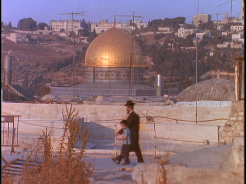 A Jewish man and his son walk past the Dome of the Rock in Jerusalem Footage