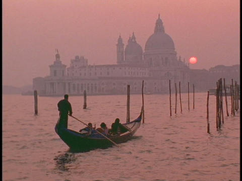 A gondolier guides a gondola across the sea approaching Venice at golden hour Footage
