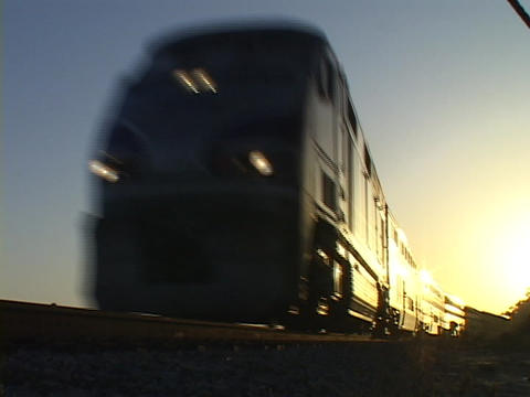 An Amtrak passenger train travels down tracks from a low angle Footage