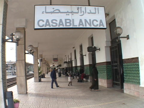 Pedestrians pass under the Casablanca train station sign Stock Video Footage