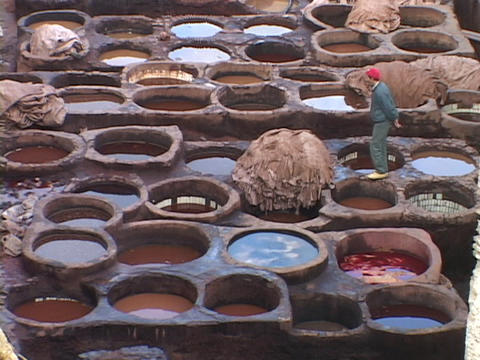 Workers dye leather in ancient pots Stock Video Footage
