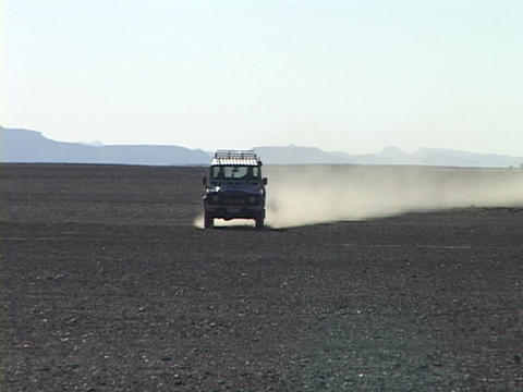 A Range Rover Land Cruiser speeds across a desert throwing up dust Footage