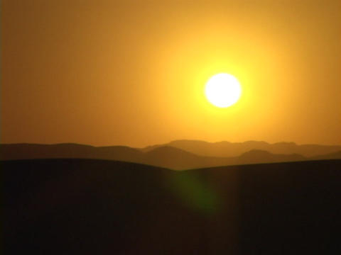 A desert silhouettes against an orange sky Stock Video Footage