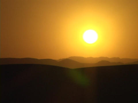A desert silhouettes against an orange sky Footage