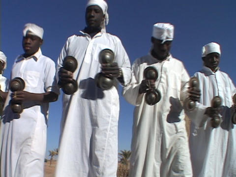 A group of Sudanese men in kaftans play cymbal-like instruments Footage