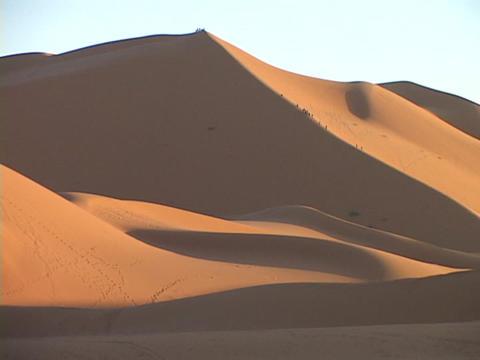 A distant caravan climbs up a huge sand dune Stock Video Footage