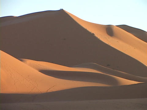 A distant caravan climbs up a huge sand dune Live Action