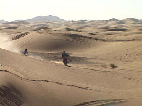 motorcyclists travel across the desert Footage
