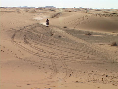 A motorcyclist rides across sand dunes Footage