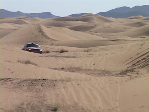 A rally car speeds through sand dunes Stock Video Footage