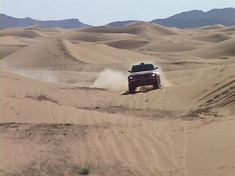 A rally car speeds through sand dunes Footage