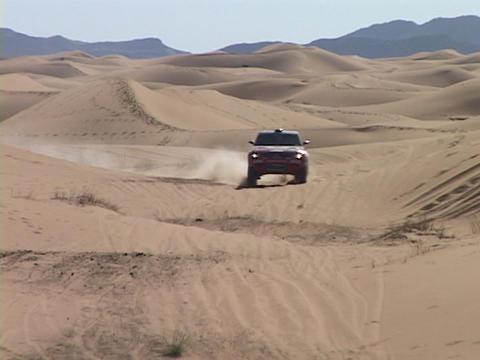 A rally car speeds through sand dunes Stock Video Footage