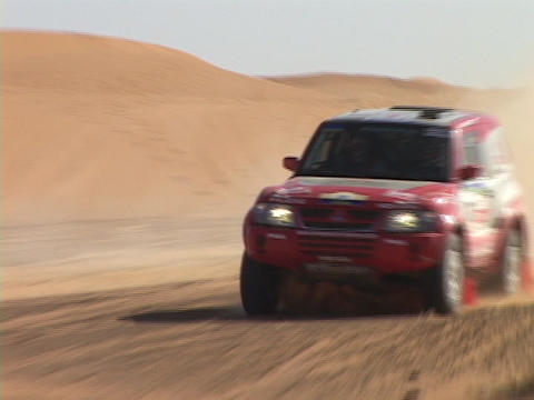 A rally car speeds around a sand dune and out of sight Stock Video Footage