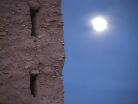 The hot sun blazes in the clear blue sky next to a mud building Footage