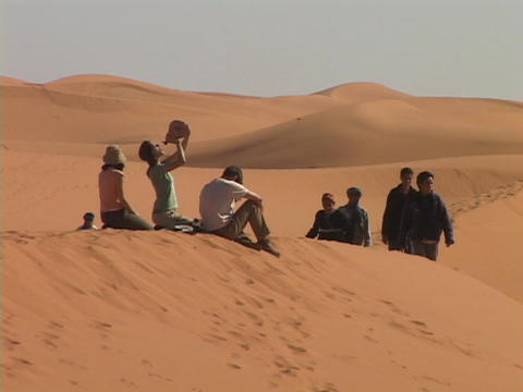 Spectators sit and drink while others walk along sand dunes as they wait for rally racers to pass by Footage