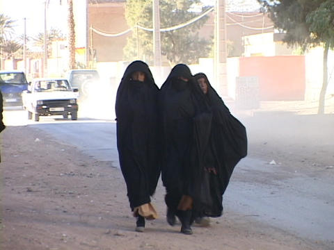Women walk along a busy street dressed in burqas Stock Video Footage