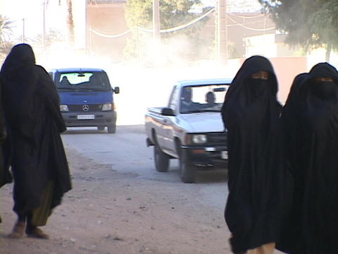 Women walk along a busy street dressed in burqas Footage
