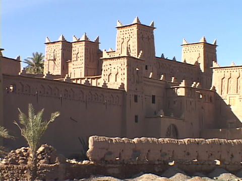 A stone wall surrounds a city in the Morocco desert Footage