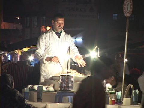 A chef stirs while he cooks his food and summons... Stock Video Footage