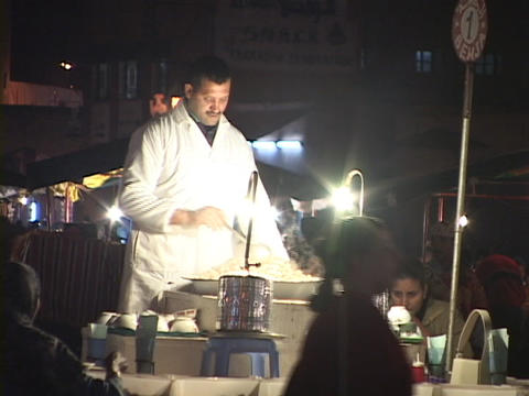 A chef stirs while he cooks his food and summons customers to his station Footage