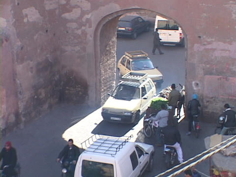 way traffic struggles to fit through a small tunnel on a busy street in Marrakesh Morocco Footage