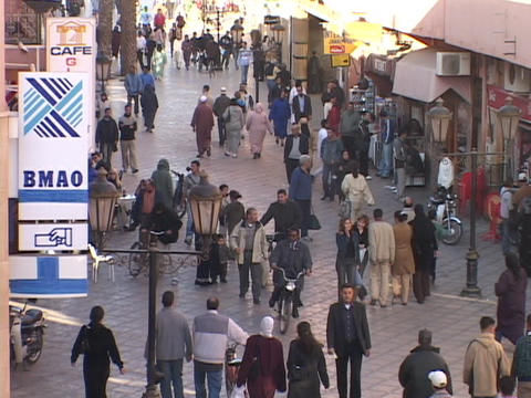 Pedestrians in modern and traditional dress walk along a... Stock Video Footage