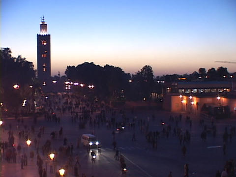 Pedestrian and cars traffic travel on a busy city street in Marrakesh Morocco Footage