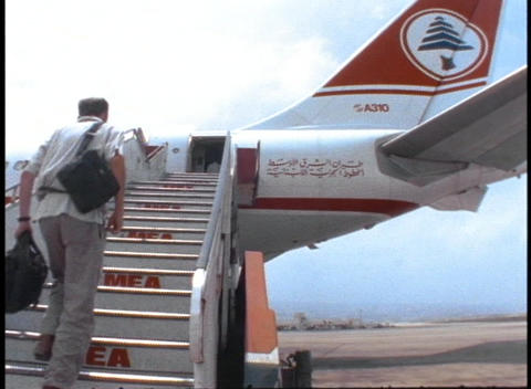 A passenger climbs the stairs to board a Middle East... Stock Video Footage