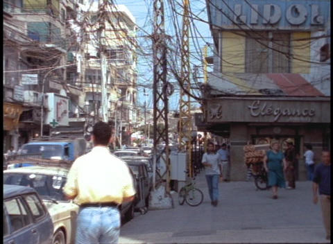 Pedestrians walk down a Beirut street beneath a tangle of... Stock Video Footage