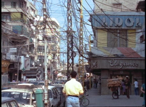 Pedestrians walk down a Beirut street beneath a tangle of electrical wires Footage