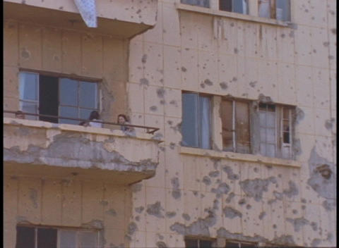 Tenants sit on the balcony of a war damaged apartment building Footage