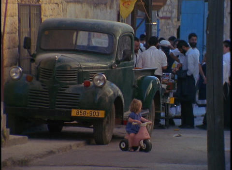 A toddler rides a little scooter in an Orthodox Jewish... Stock Video Footage
