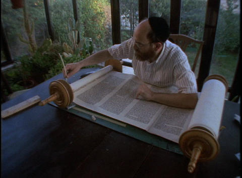 An Orthodox Jewish scribe works on writing a Torah scroll Footage