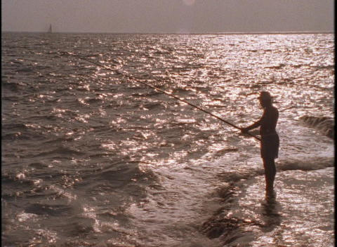 A fisherman stands beside the sea at golden hour Stock Video Footage