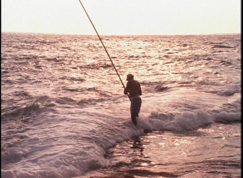 A fisherman stands in heavy surf at golden hour Stock Video Footage