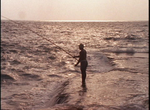 A fisherman stands in heavy surf at golden hour Footage