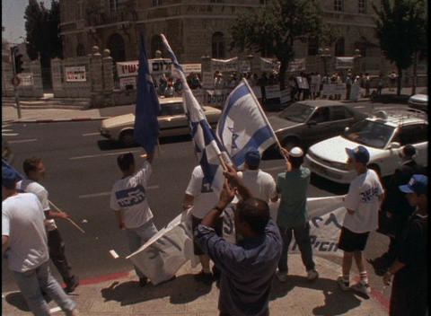 Protesters wave Israeli flags at a large demonstration... Stock Video Footage