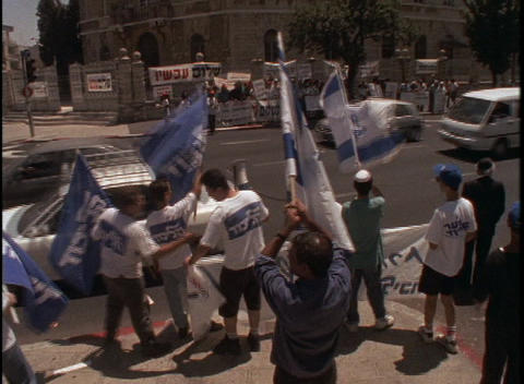 Protesters wave Israeli flags at a large demonstration near the Knesset in Israel Live Action