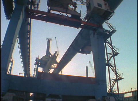 A massive crane moves shipping containers at a port while... Stock Video Footage